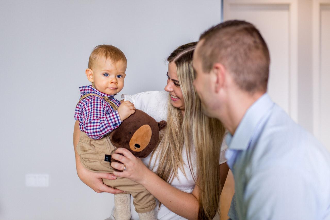 dziecko w szelkach, pluszowy misio, mama i tata